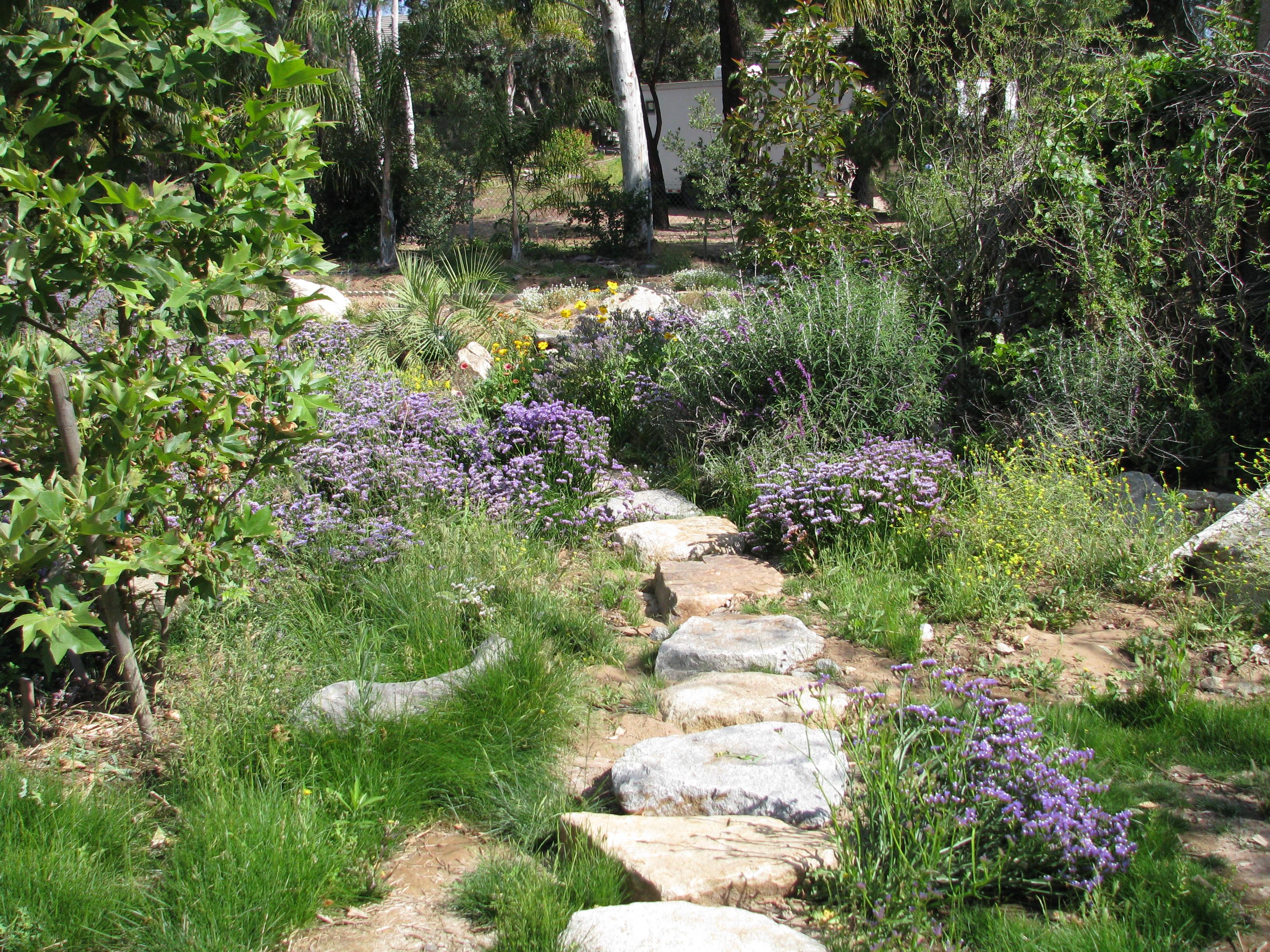 Status and wildflowers across the stone walkway | Vegetariat