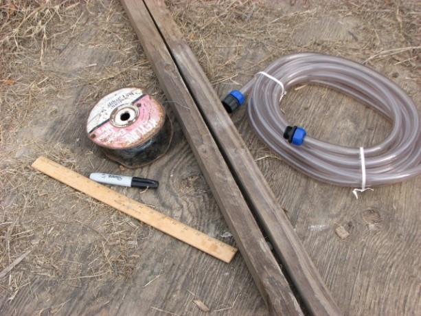 You will need two slim posts, 30' of tubing (the only kind I could buy in town was for cleaning fishtanks, hence the threaded ends.  You don't need these!), a ruler, wire and a waterproof marker.